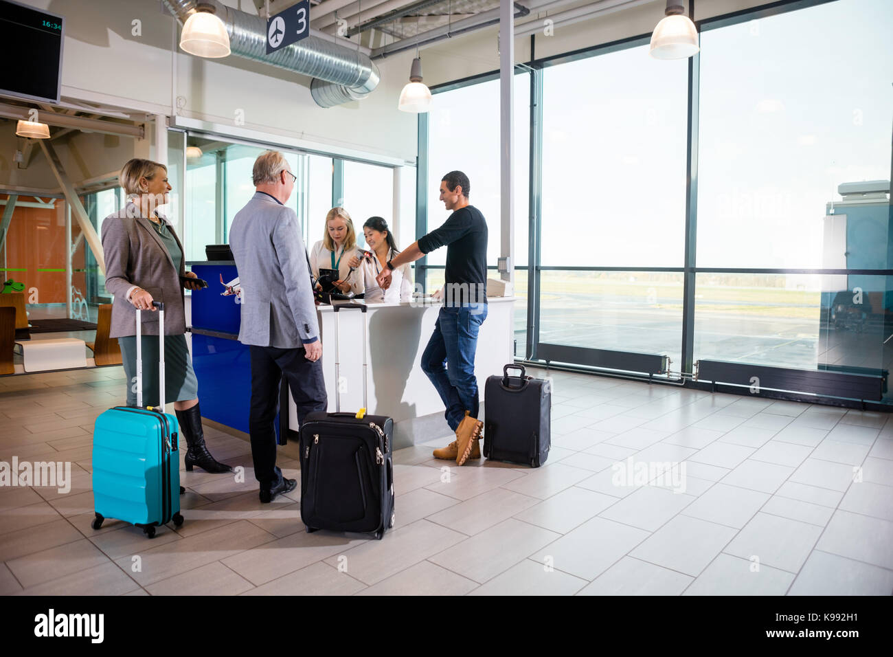 Passengers With Luggage Standing While Receptionists Working At  - Stock Image