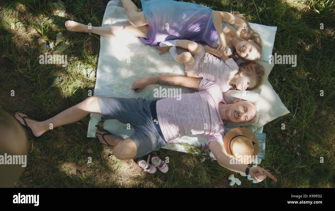 Family is resting in park - father, mother and daughter have breakfast - top view - Stock Image
