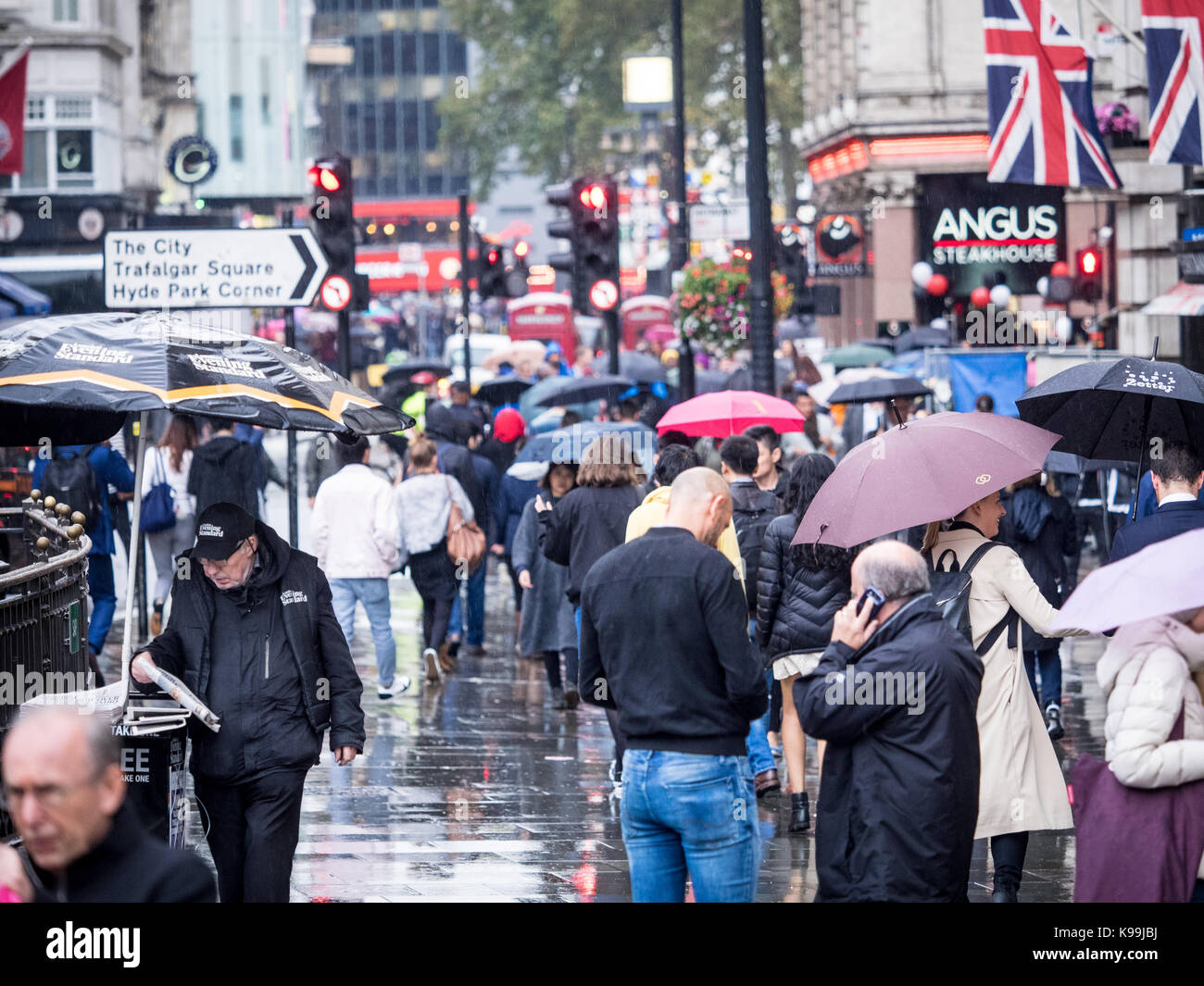 London in the Rain - tourists and workers brave the rain near London's Leicester Square in Soho - Stock Image