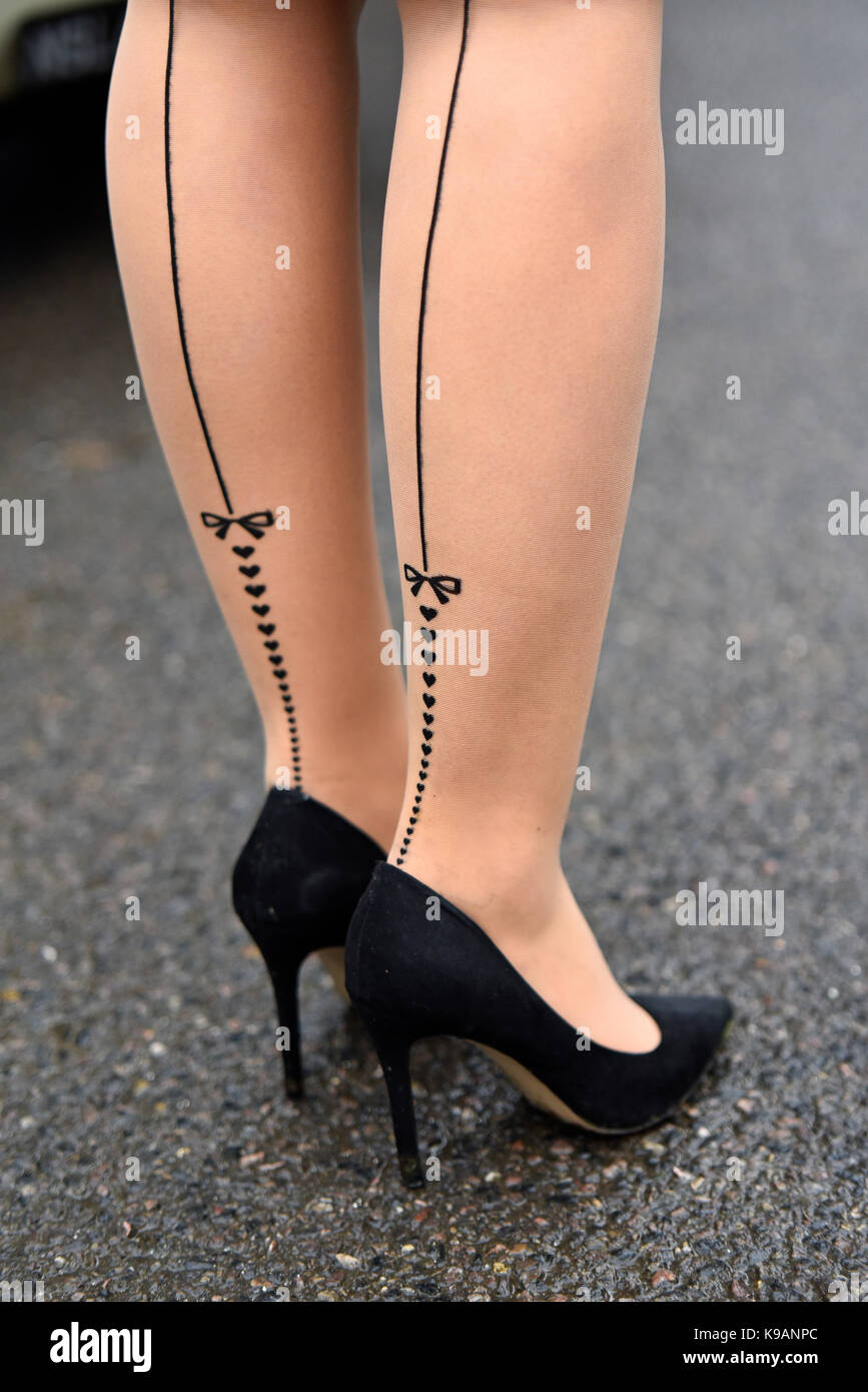 Female legs in heart and bow nylons at the Goodwood Revival 2017. Space for copy - Stock Image