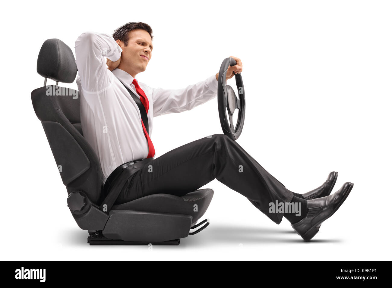 Elegant man seated in a car seat experiencing neck pain isolated on white background - Stock Image
