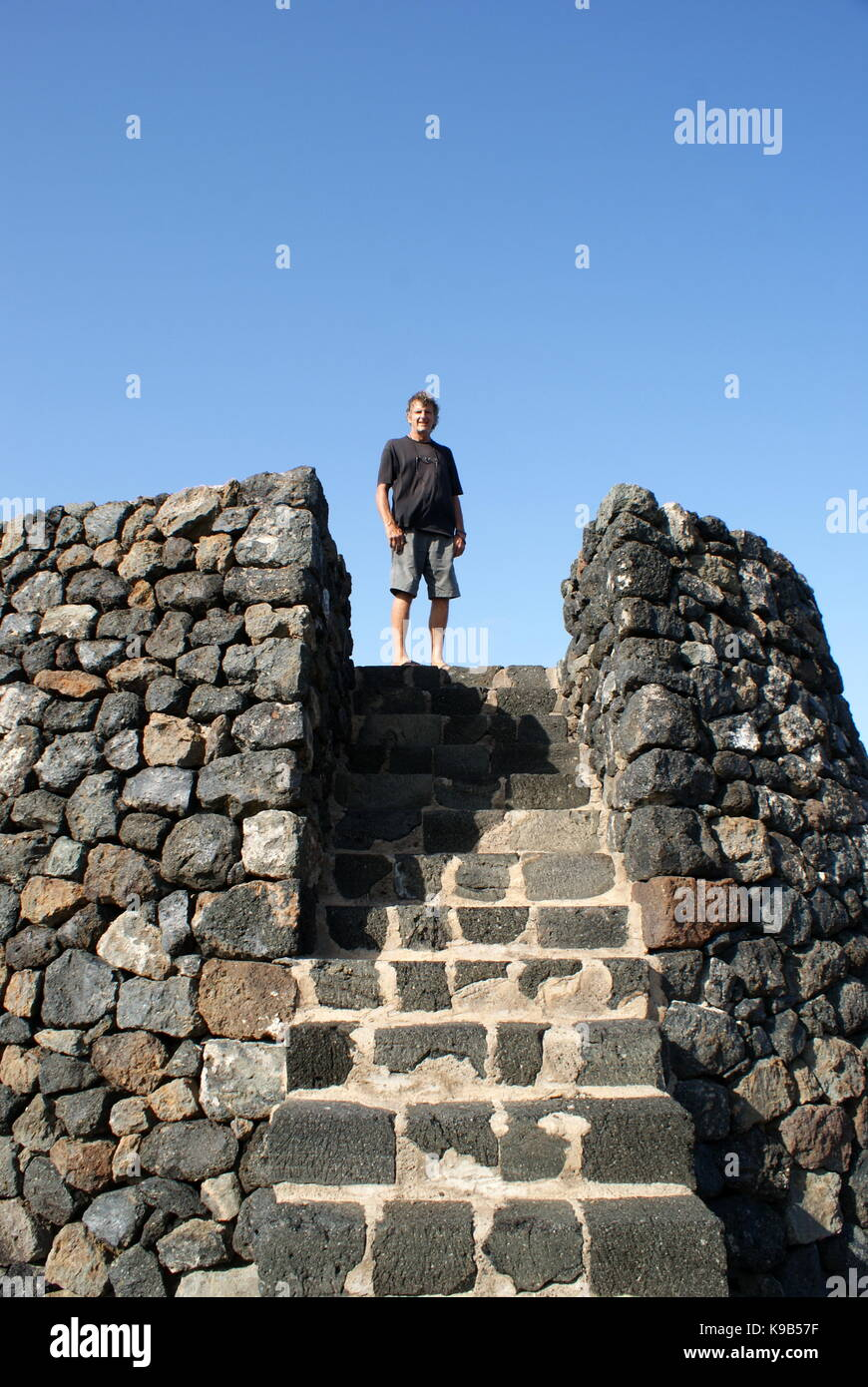 Man standing at the top of a black stone tower, Pantelleria - Stock Image