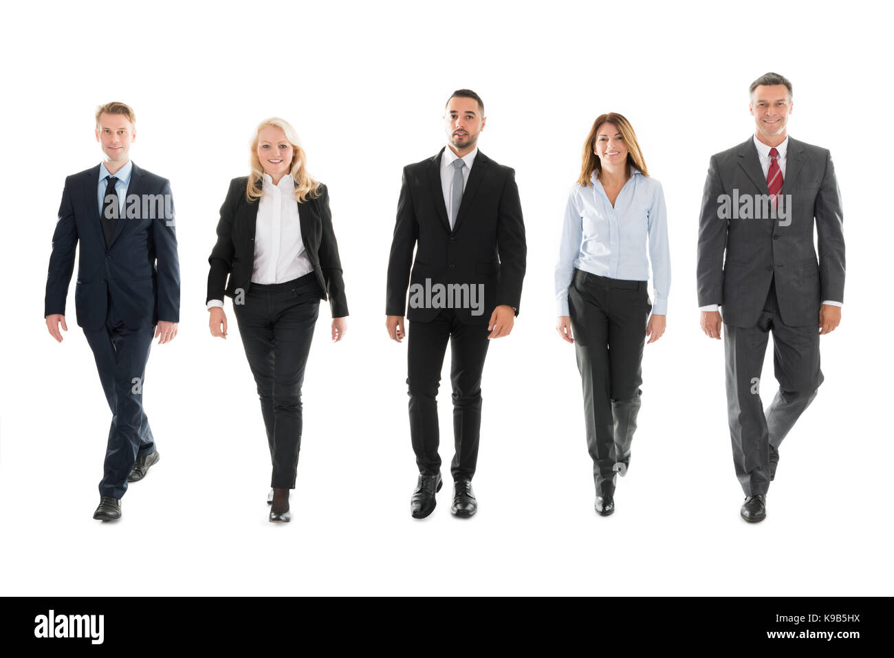Full length portrait of confident business people walking against white background - Stock Image