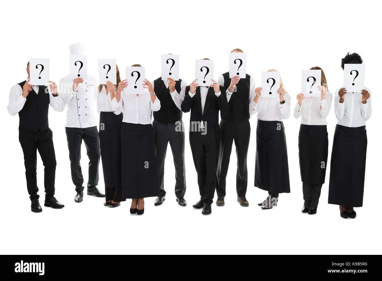 Full length of restaurant staff hiding faces with question mark signs against white background - Stock Image