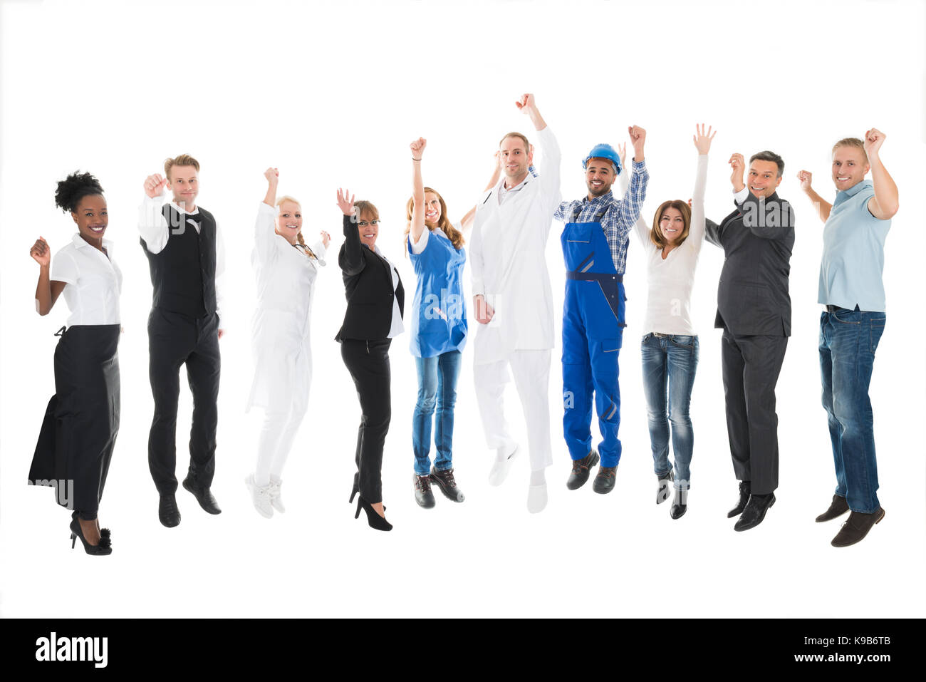 Full length portrait of people with various occupations cheering against white background - Stock Image