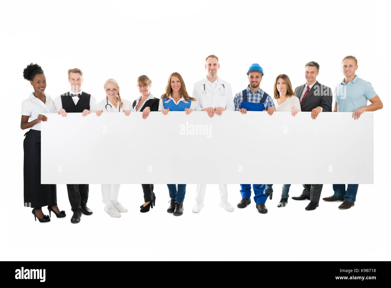 Group portrait of people with various occupations holding blank billboard against white background - Stock Image