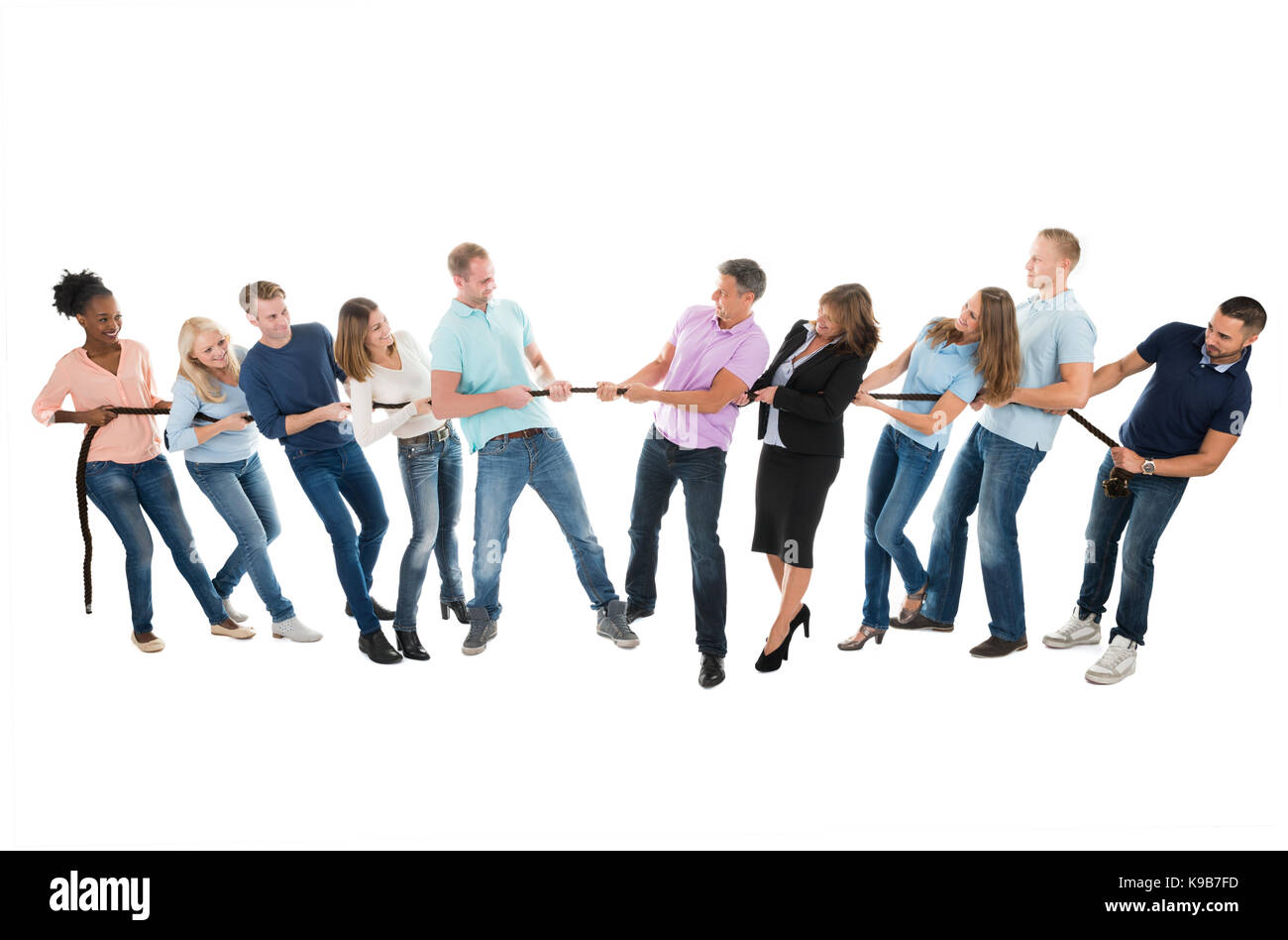 Full length of multiethnic creative business teams playing tug of war against white background - Stock Image