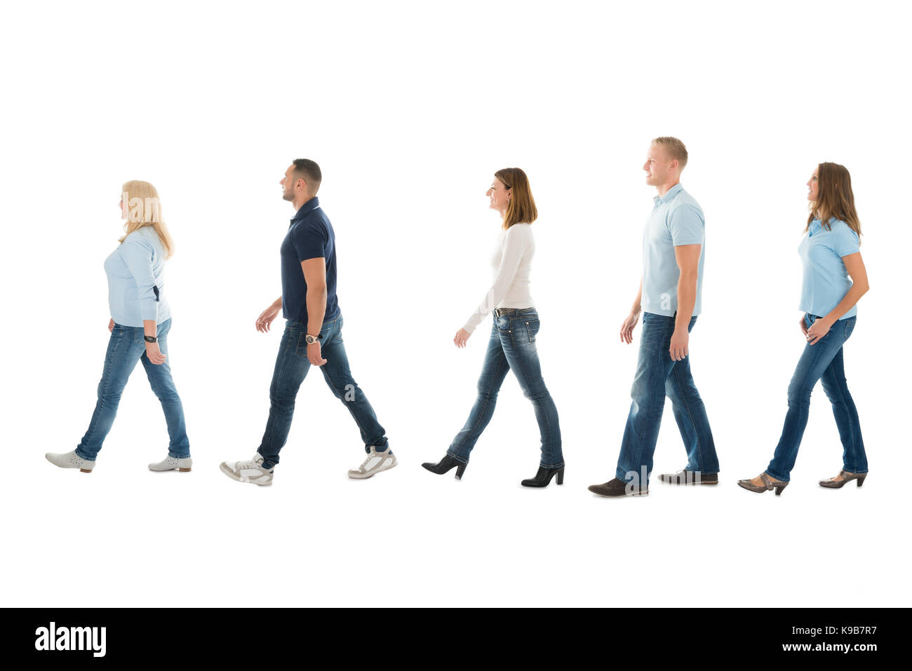 Full length side view of men and women walking in queue isolated on white background - Stock Image