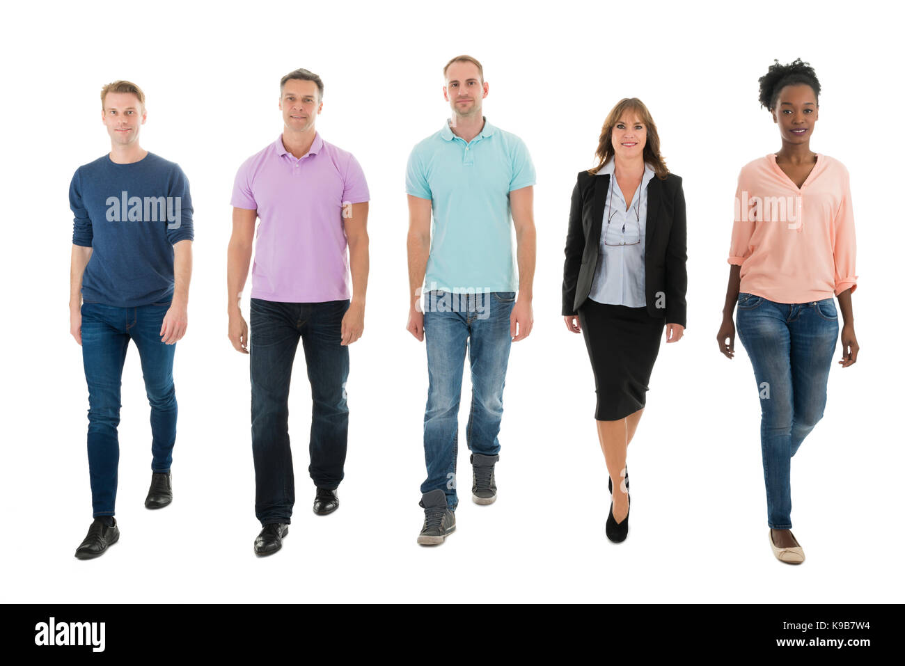 Full length portrait of creative business people walking with manager against white background - Stock Image