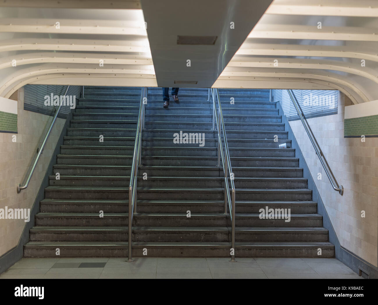 A pair of shoes appears at the top of a stairwell leading to the PATH Tubes in Hoboken Stock Photo