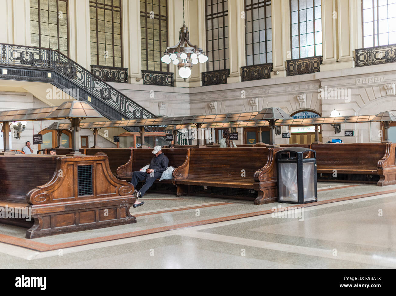 Hoboken, NJ USA -- September 19, 2017 The waiting room for the Hobaoken train station. A man is alseep on one of - Stock Image