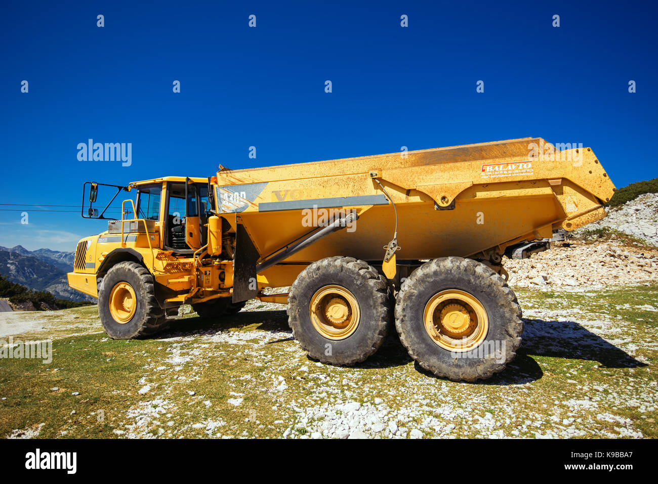 VOGEL MOUNTAIN, SLOVENIA - AUGUST 30, 2017: Construction machinery for crushing stone, large Volvo truck dumper - Stock Image