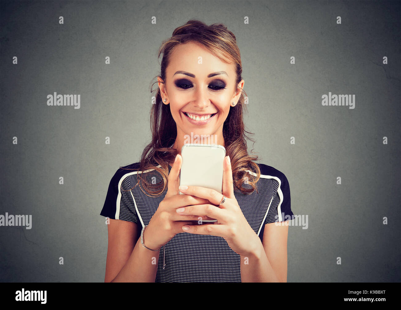 Young smiling woman using a mobile phone - Stock Image