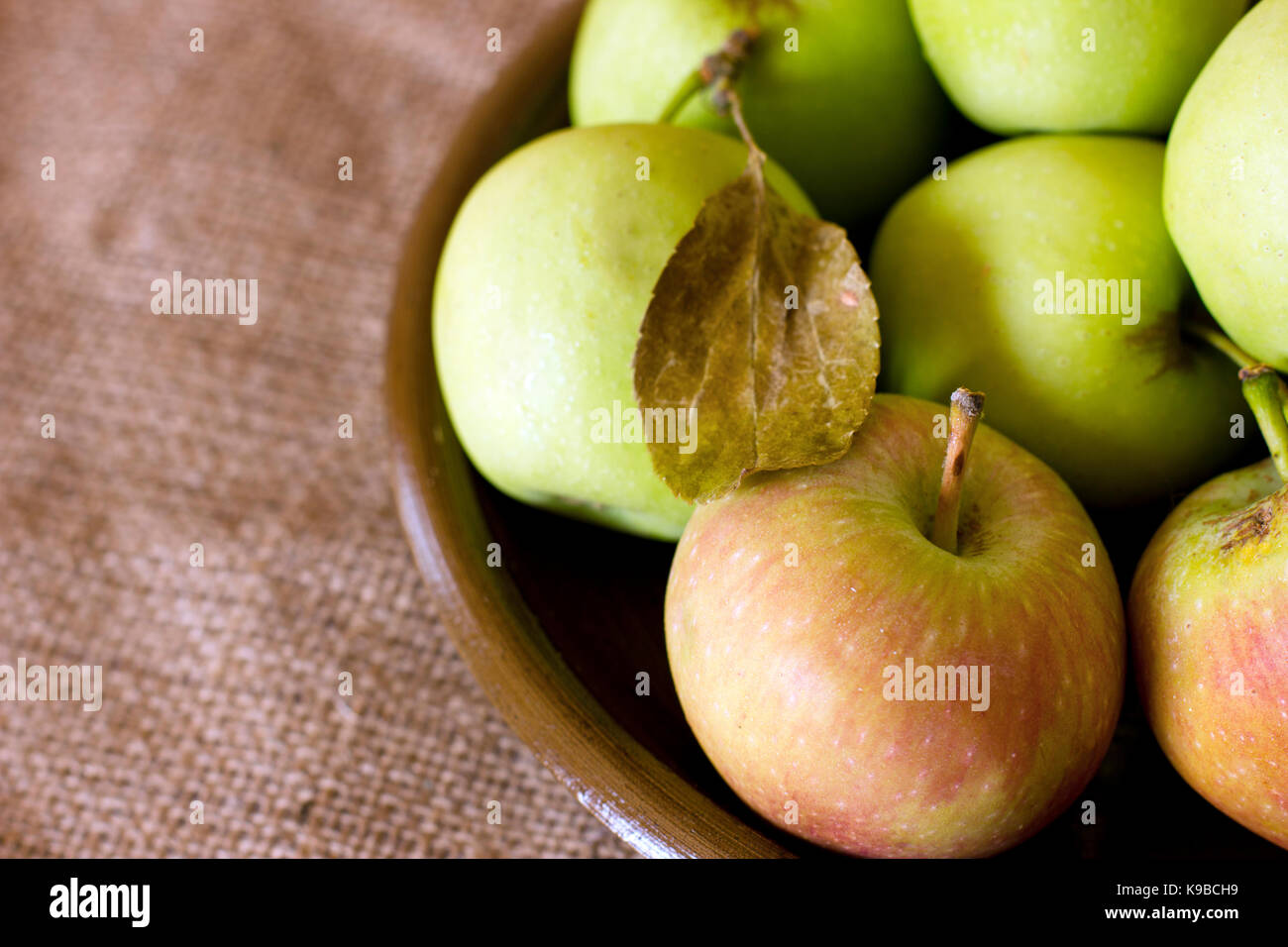 Green and red garden apples on the clay brown dish - Stock Image