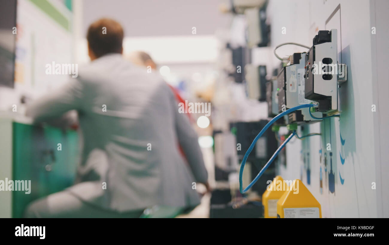 People working in high-tech industry room near electronic equipment - Stock Image