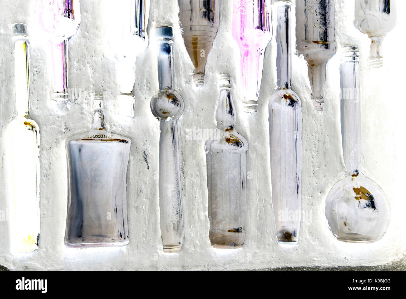 Bottles in a wall - glass bottles embedded in a white washed wall - Stock Image