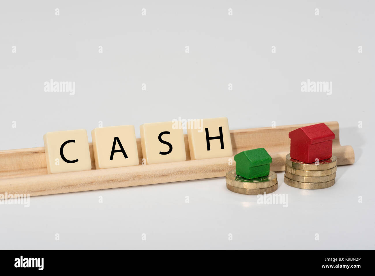 Finance related word spelt out with letter tiles. Isolated on white background with wooden toy houses on top of - Stock Image