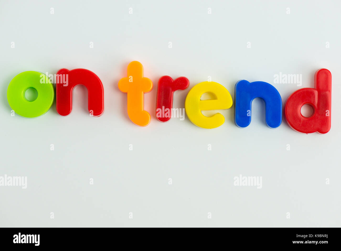 on trend word in colourful children's letters - Stock Image