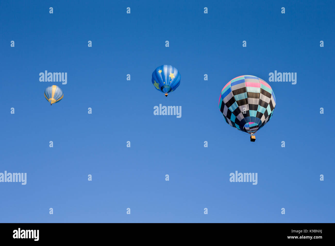 Three colorful hot air balloons set against a clear blue sky.  Seen from below.  Room for copy in the sky. Stock Photo