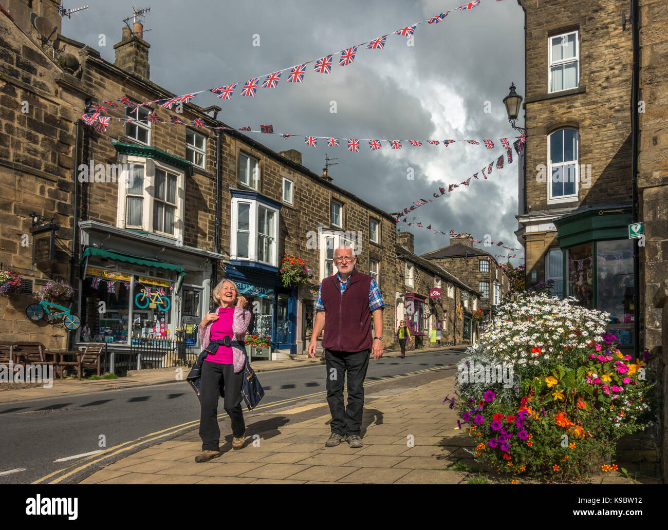 Two mature adults (70-80) walking the colourful High Street of Pateley Bridge market town with bunting strung across - Stock Image