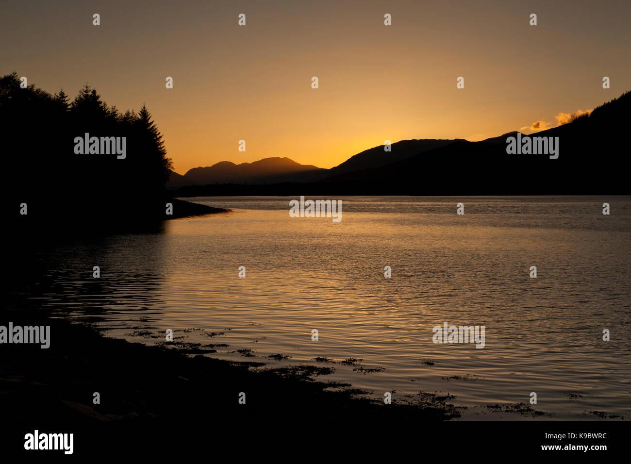 Sunset behind the hills and mountains of North Ballachulish, Glencoe, Scotland, UK - Stock Image