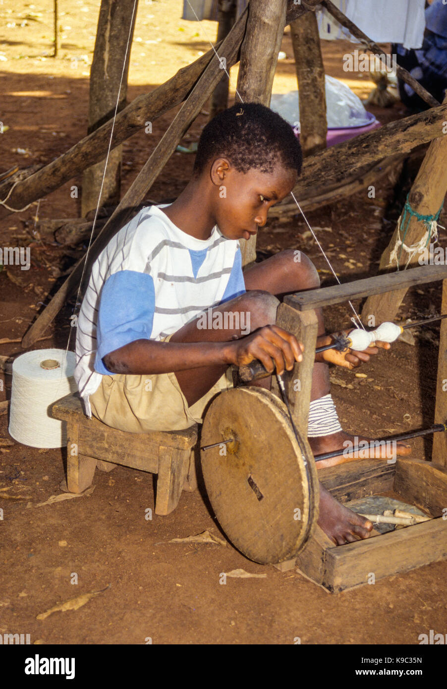 Ivory Coast, Cote d'Ivoire.  Young Senoufo Boy Spinning Thread on a Spindle. - Stock Image