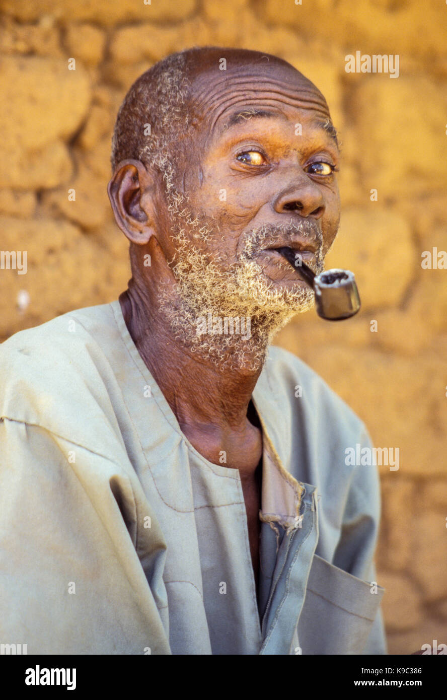 Tabakala, Ivory Coast, Cote d'Ivoire.  Senoufo Man with his Pipe. - Stock Image