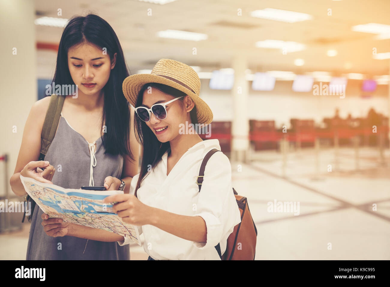 Happy women tourist on map to  the airport vacation.Travel concept. - Stock Image
