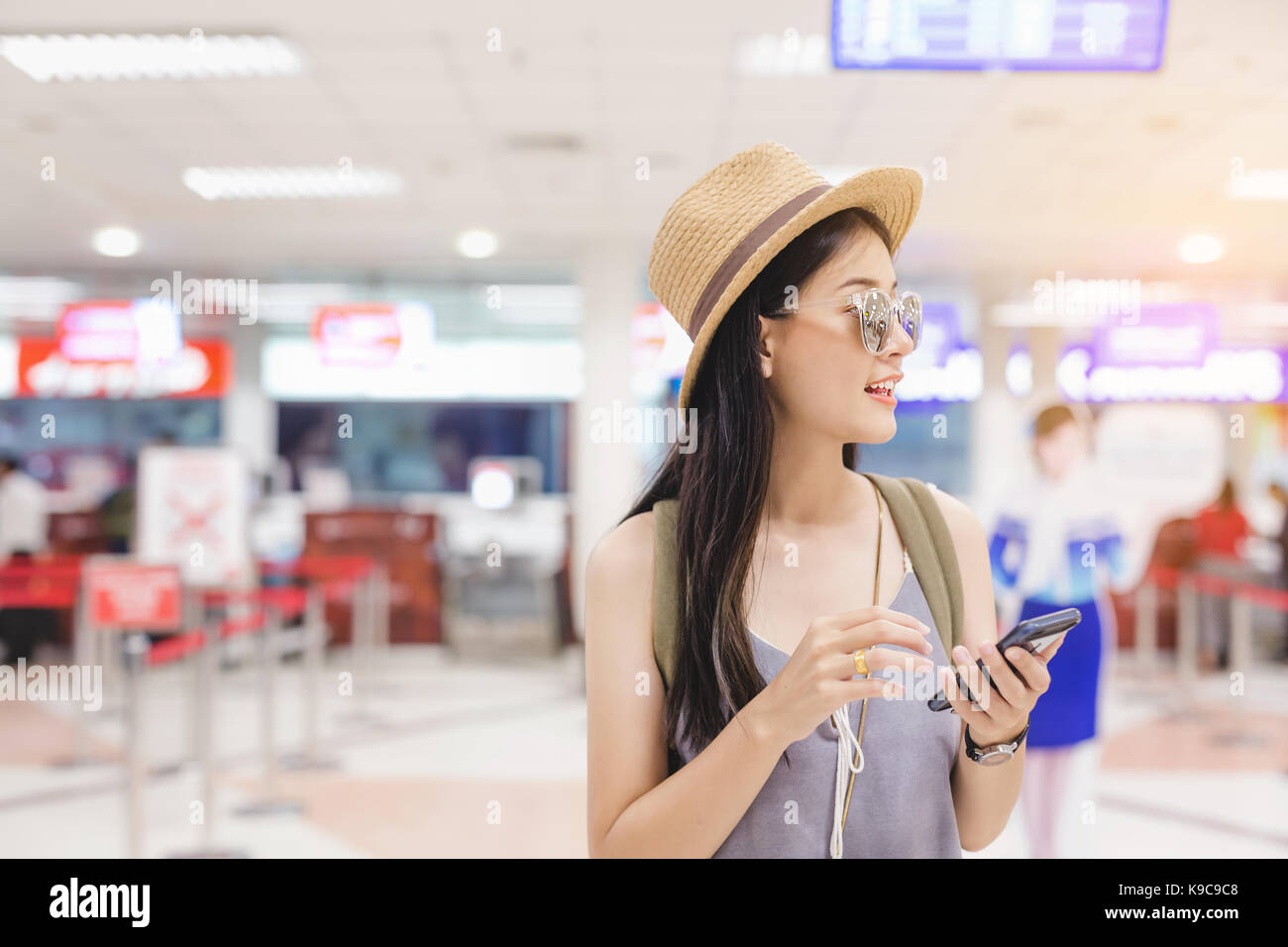 Female  check flight on smart phone at airport.Travel concept. - Stock Image