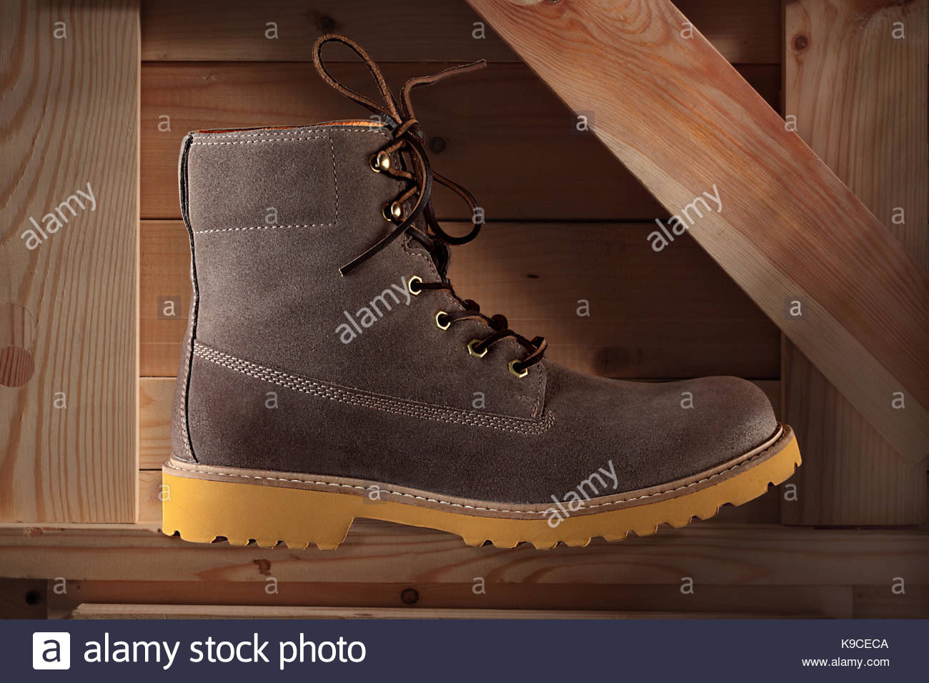 studio still life of a suede safety boot  on a wooden backgroun - Stock Image