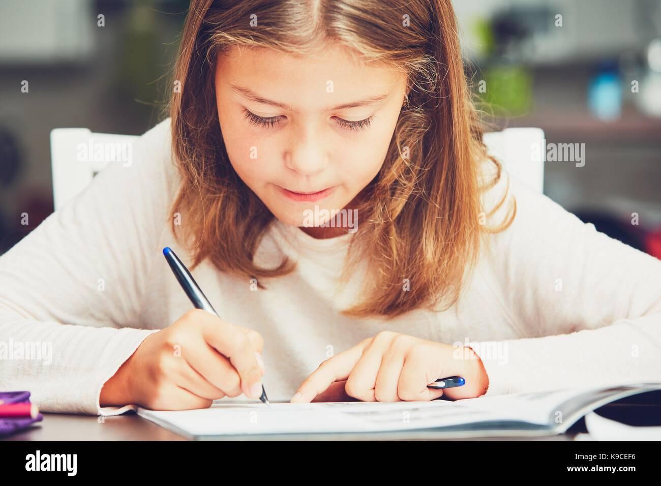 Little girl writing his homework for elementary school. - Stock Image