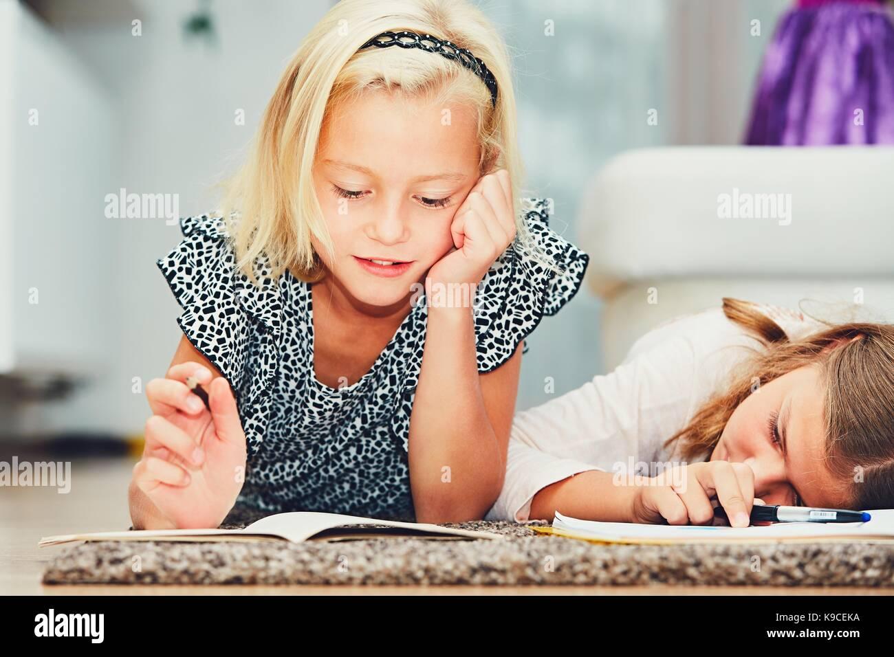 Girls lying on the carpet making their homework in elementary school. - Stock Image