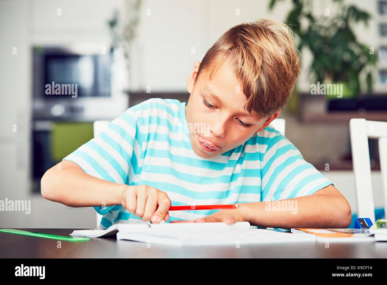 Little boy writing his homework for elementary school. - Stock Image