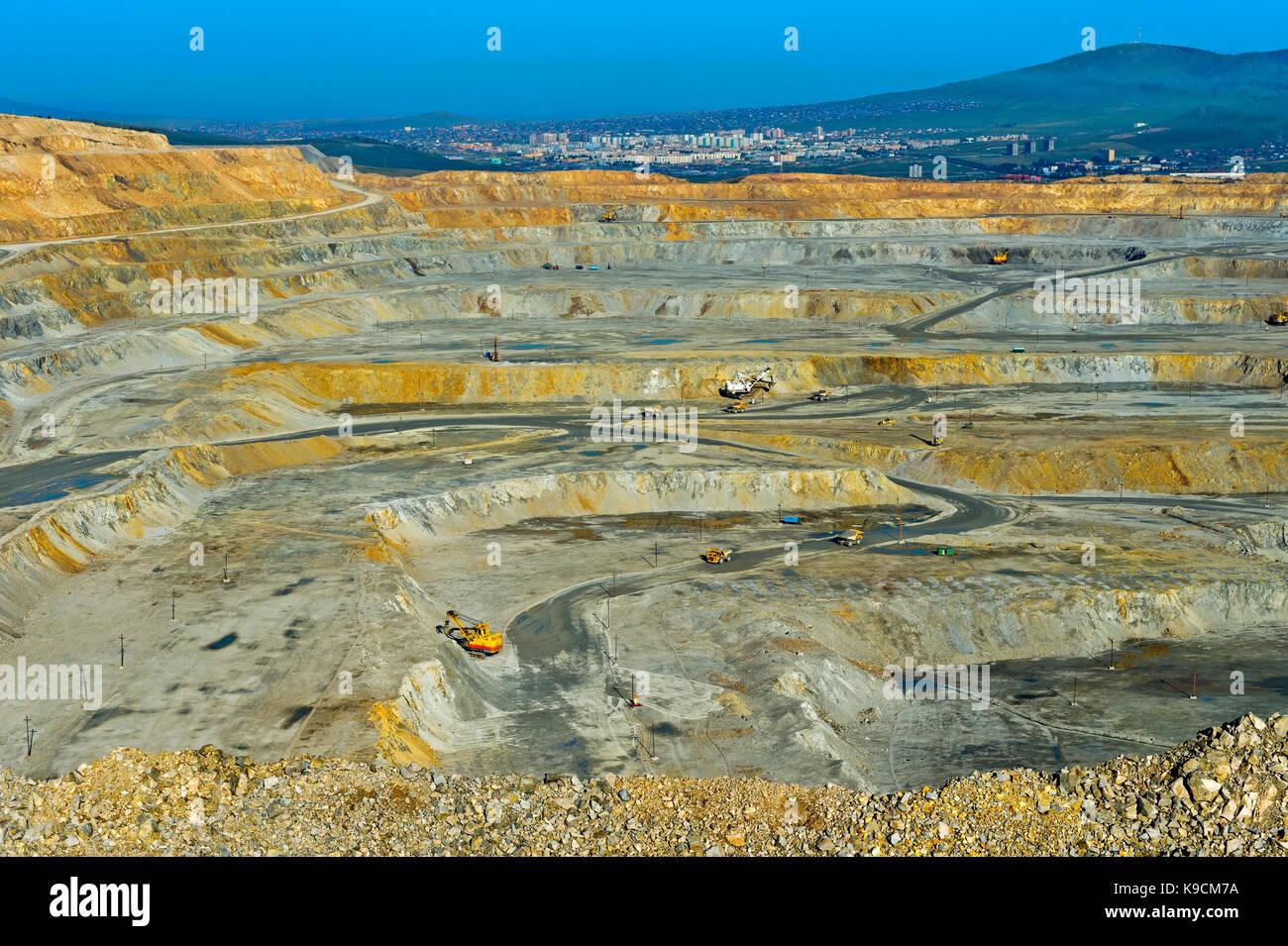 Benches of an open-pit copper mine of the Erdenet Mining Corporation EMC, city of Erdenet behind, Erdenet, Mongolia - Stock Image