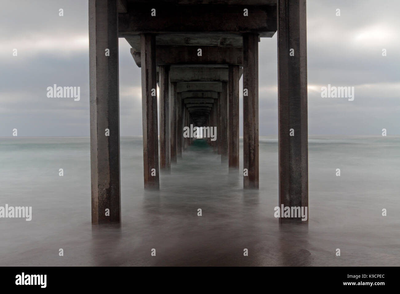 Long exposure seascape of Scripps Pier from the beach in San Diego  California with misty water and artistic perspective. - Stock Image