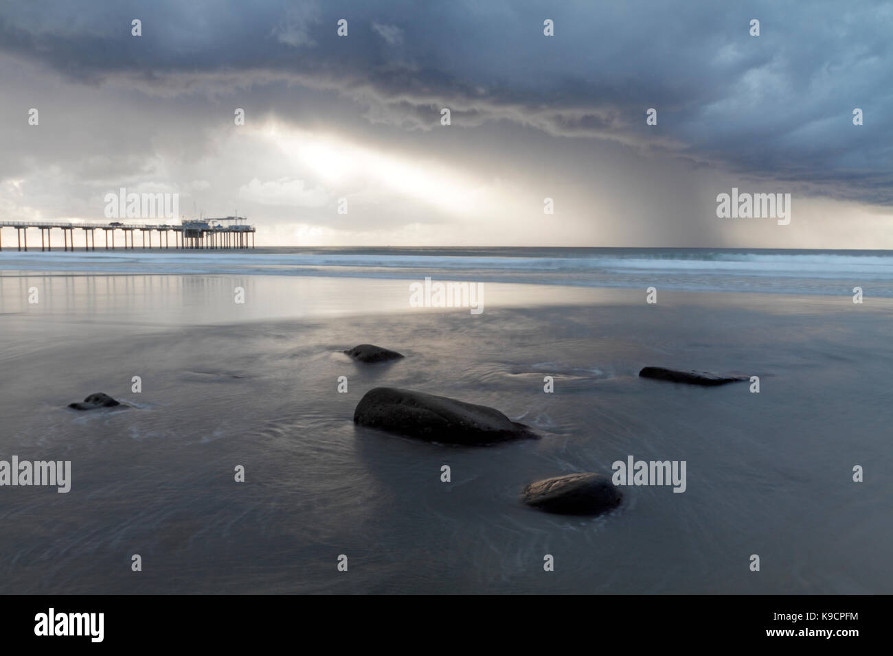 Scripps Pier, La Jolla, San Diego, viewed during a rainstorm from the beach with rocks in the foreground and dramatic - Stock Image