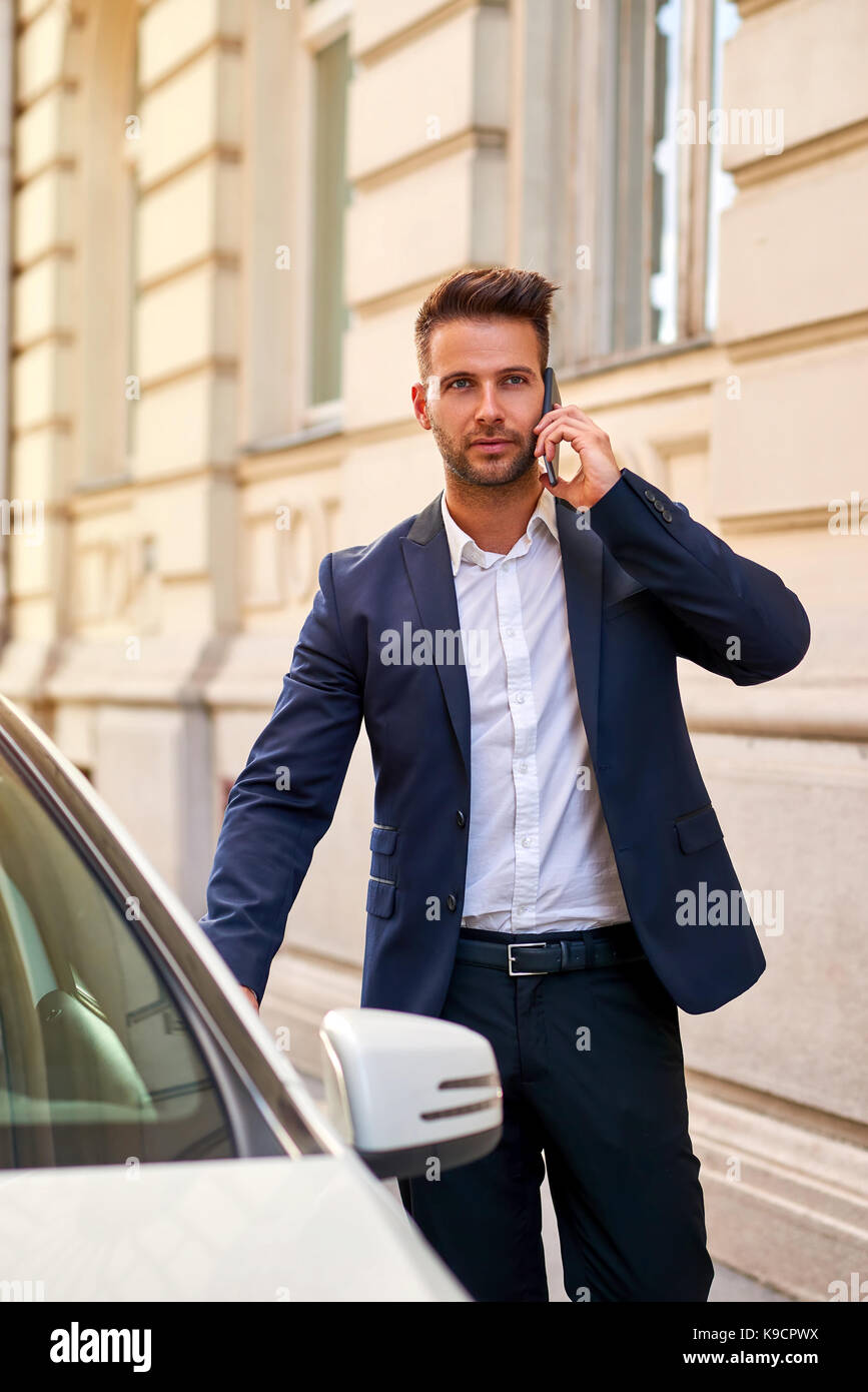8f0e04bb401d A handsome young businessman walking to his car on the street while talking  on his phone