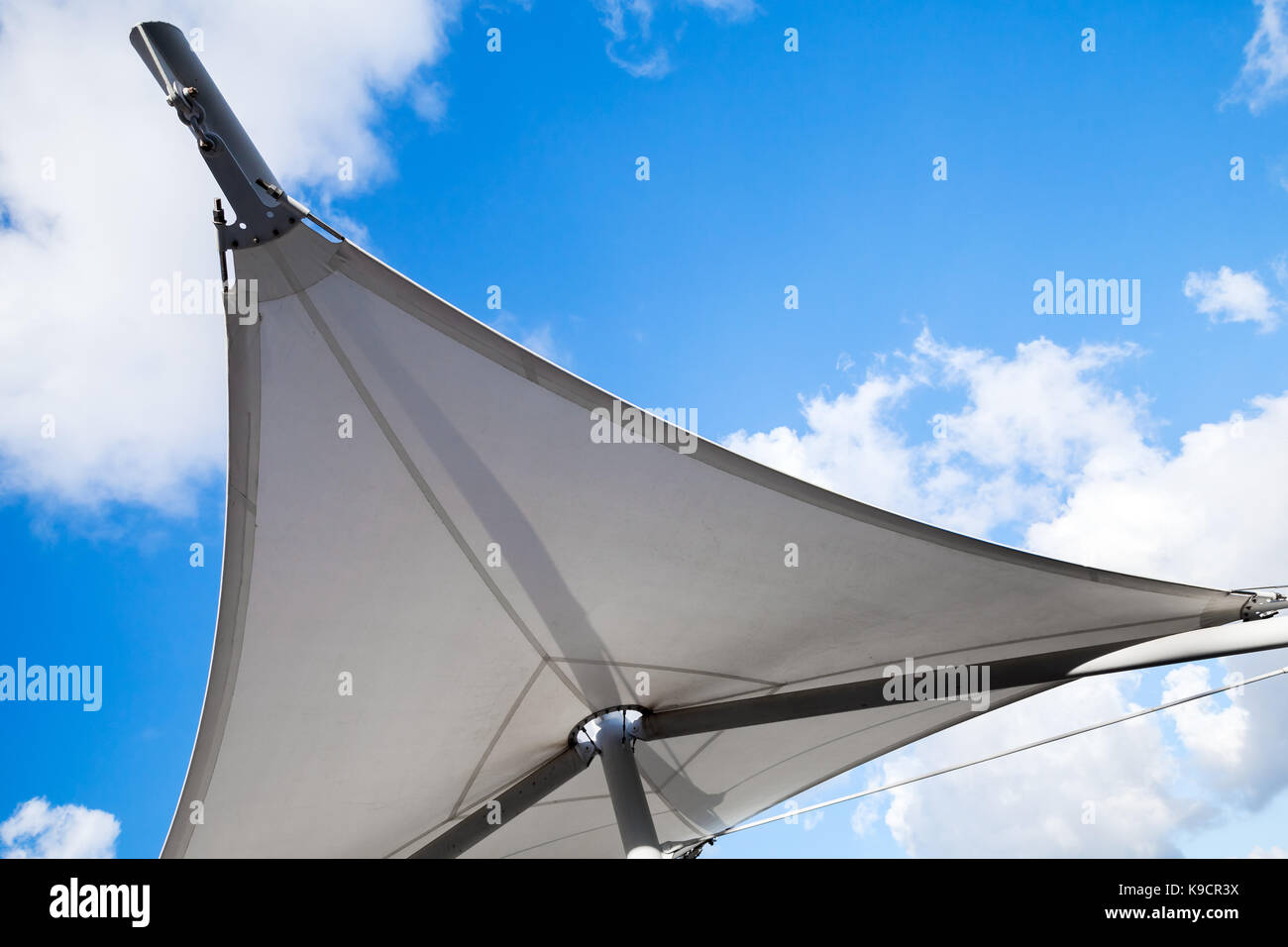 Awning in sail shape under cloudy sky background Stock Photo