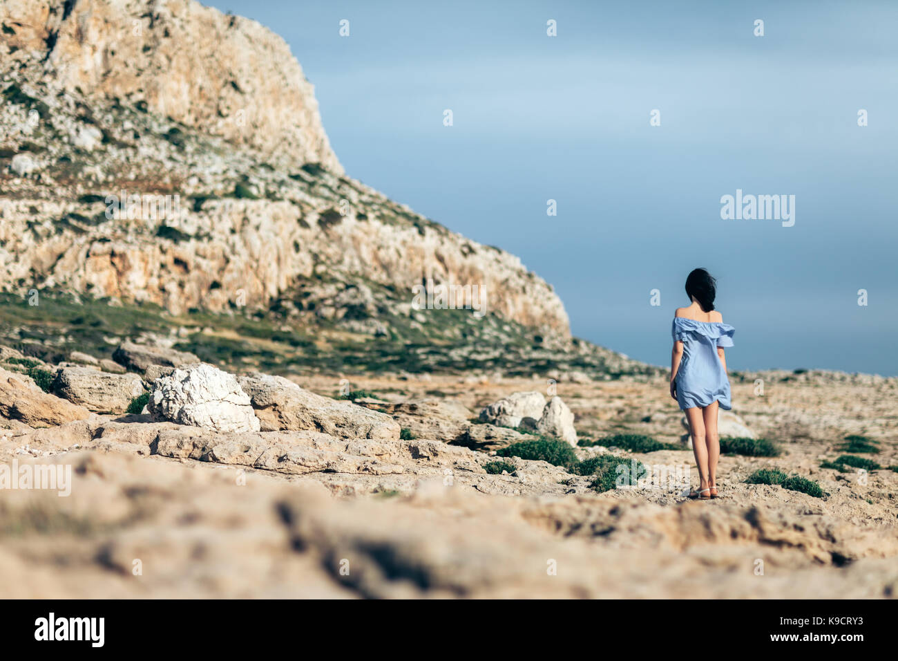 Back view of lonely woman walking on rocky desert with dramatic sky - Stock Image