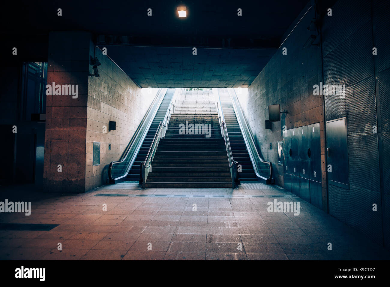 Exit with escalator from the underground metro. Light at the end of the tunnel concept - Stock Image