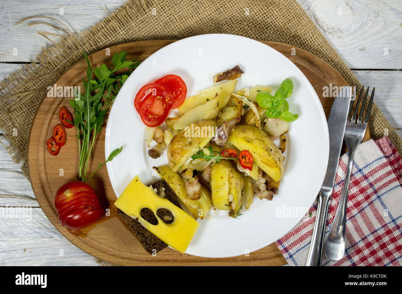 Baked potatoes at home. Potatoes on a white plate. Background burlap. - Stock Image