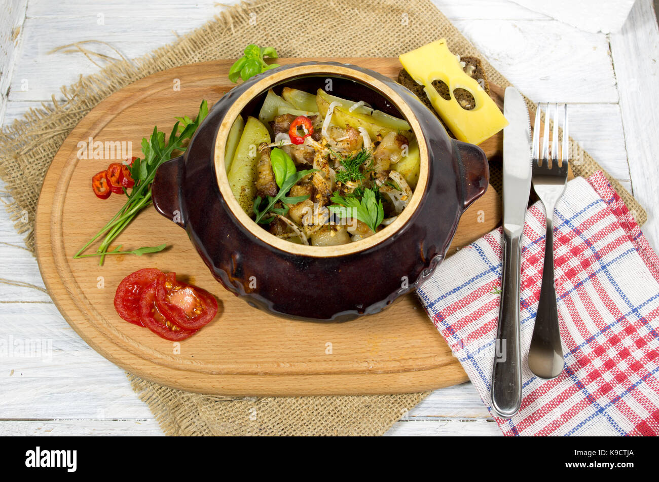 Potatoes in clay pots. Potato with bacon. Potatoes and vegetables. - Stock Image