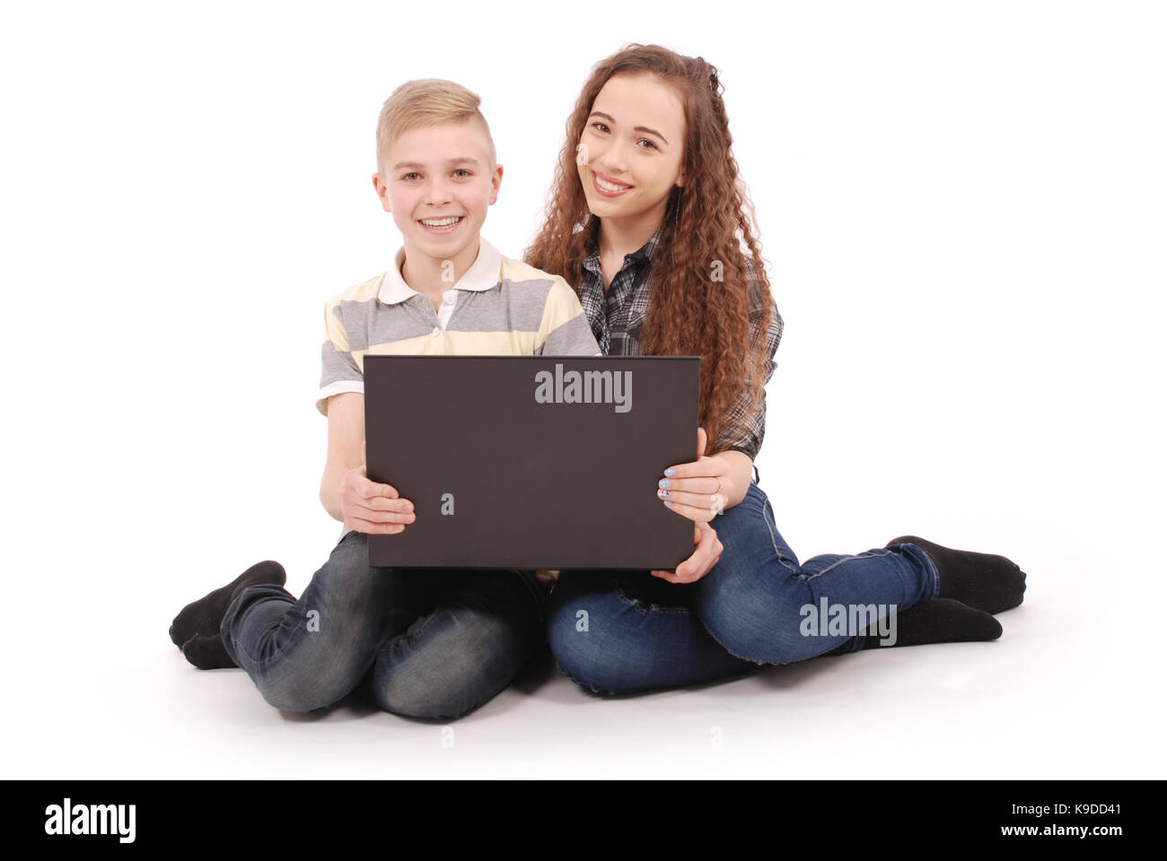 Boy and girl using a laptop isolated on white background - Stock Image