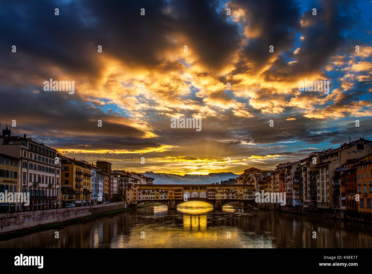Storm clouds clear at sunrise at the Ponte Vecchio in Florence, Italy - Stock Image