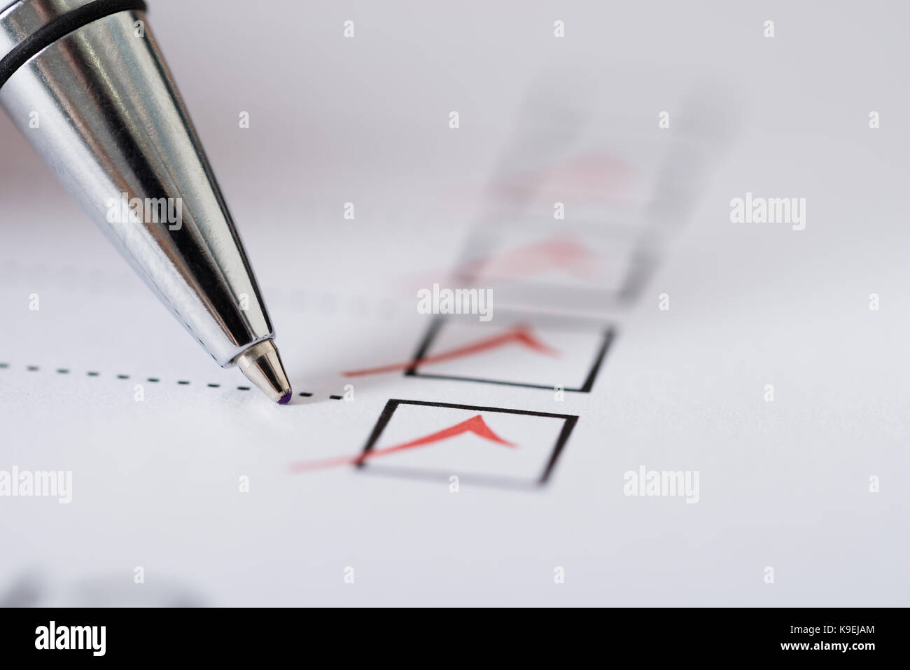 Close-up Of Silver Pen Over Filled Checkboxes In Form - Stock Image