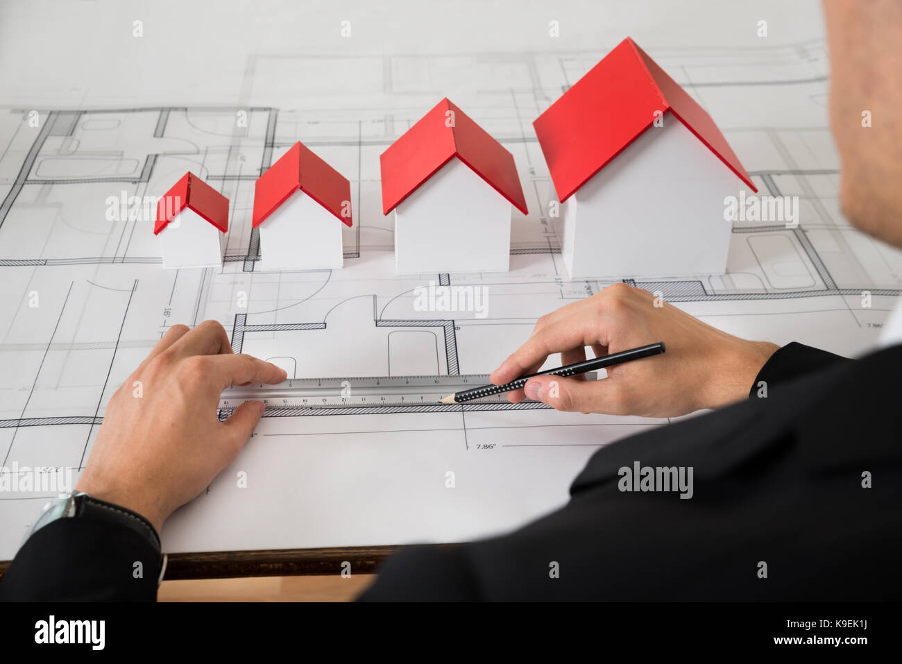 Close-up Of Architect With Different Size House Models On Blueprint In Office - Stock Image