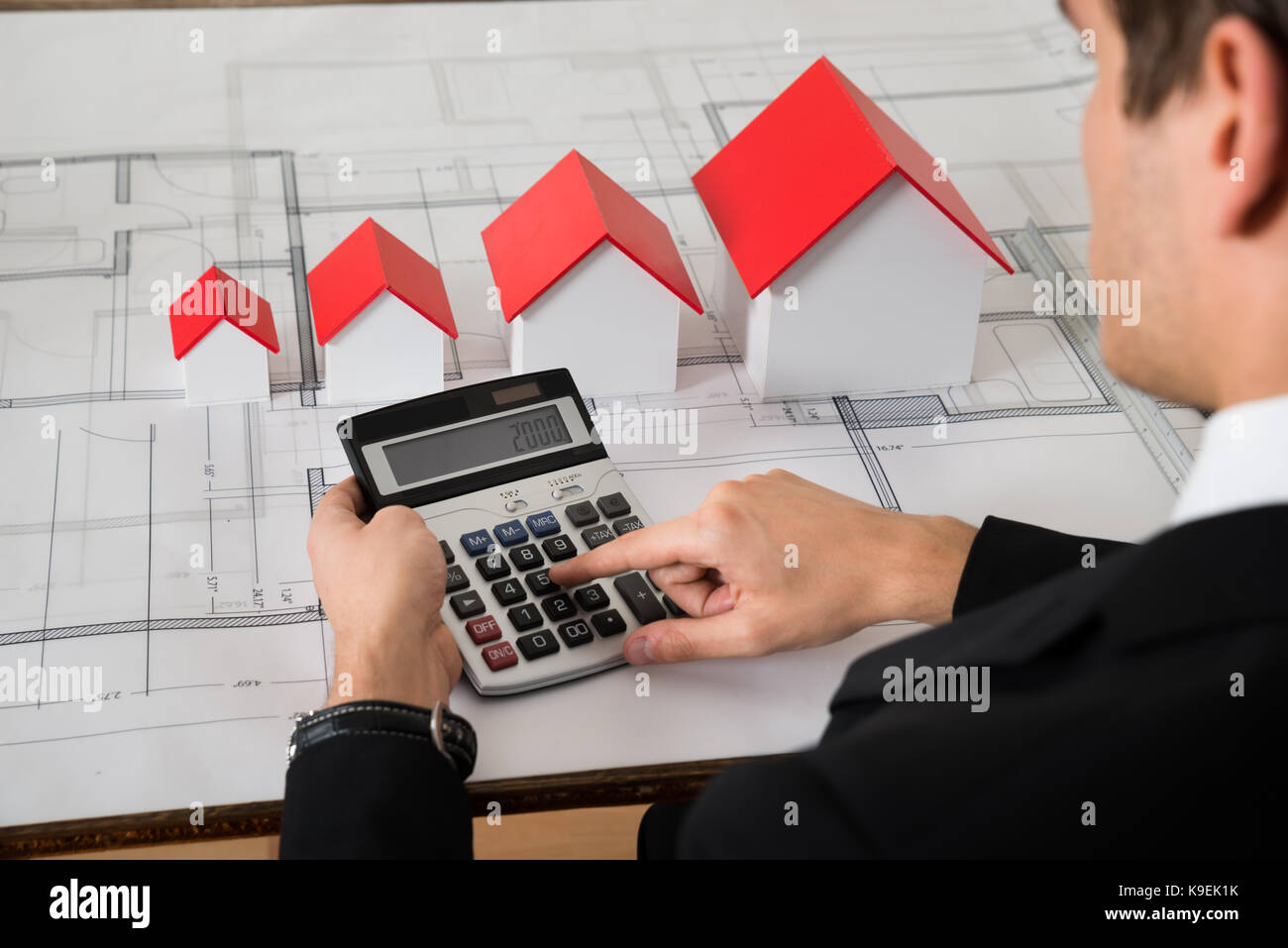 Close-up Of Male Architect Calculating In Front Of House Models On Blue Print In Office - Stock Image
