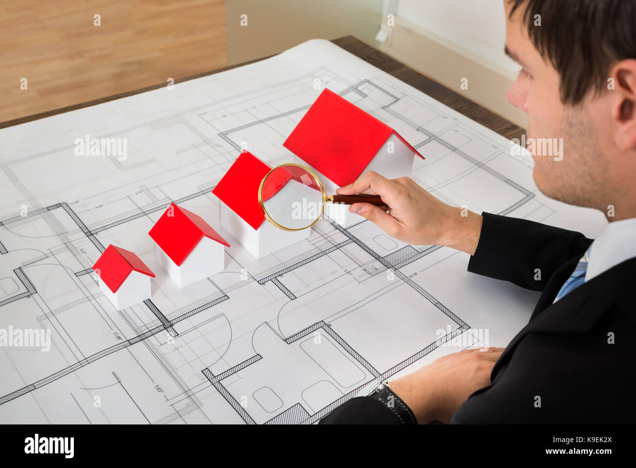 Male Architect Looking At House Models On Blueprint Through Magnifying Glass - Stock Image