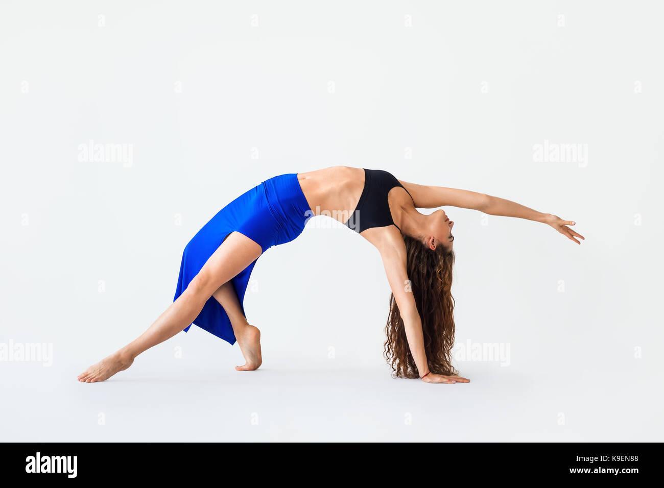 Young woman doing yoga asana Wild Thing Pose. Camatkarasana Stock