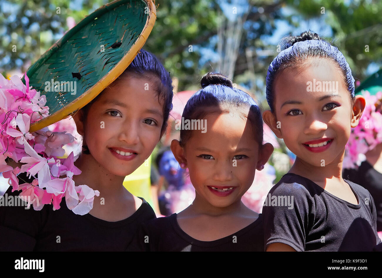 Three Filipino elementary age girls wait their turn to march in the annual multi-cultural festival parade displaying - Stock Image